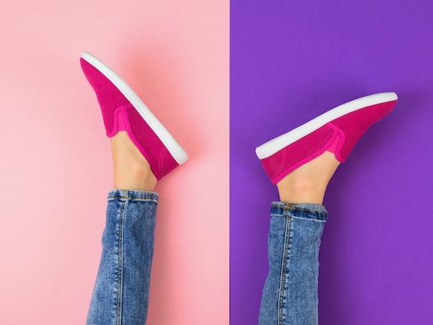 Ноги девушки в джинсах и красных кроссовках на разноцветном полу