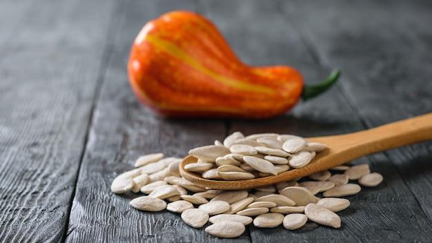 Причудливая тыква и деревянная ложка с семенами на деревянном столе.