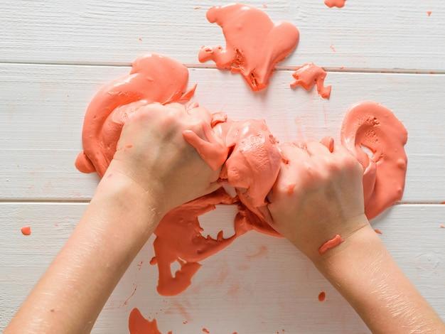Ребенок замешивает руками оранжевую улыбку на белом деревянном столе.