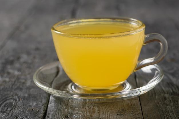 生姜の根の飲み物と黒いテーブルの上の柑橘類の受け皿とガラスのボウル。