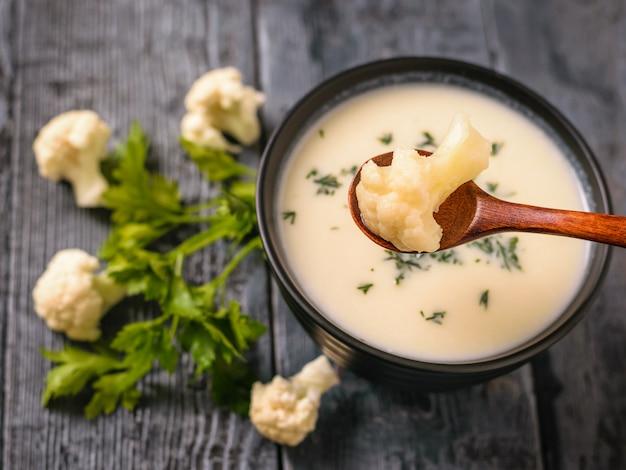 Отварная цветная капуста в деревянной ложке с кремом из капустного супа.