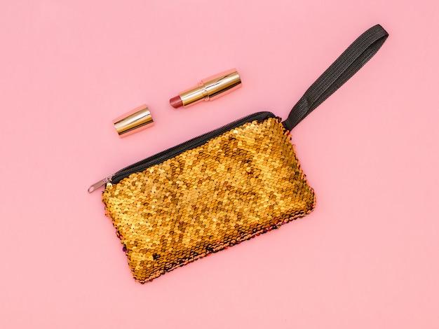 ピンクのテーブルに口紅が付いた黄金の女性のハンドバッグ