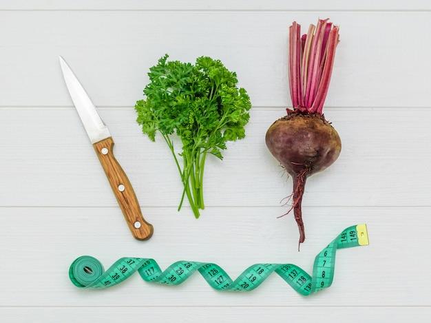 ナイフとパセリの束と白い木製のテーブルに巻尺と新鮮な赤いビーツ