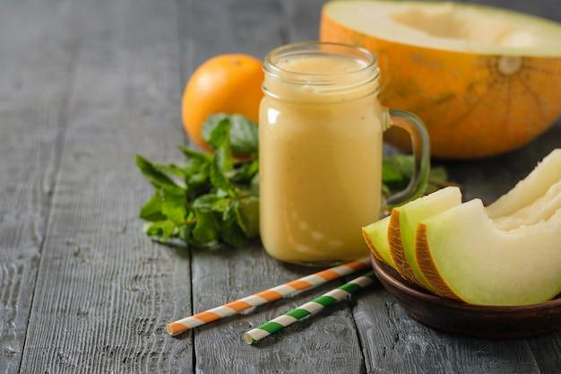 メロンのスムージー、黄色と緑のカクテルチューブ、木製のテーブルに新鮮なメロンスライス