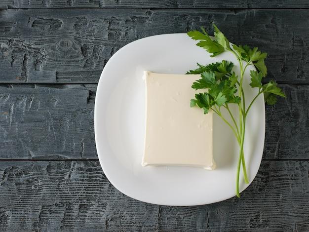 黒い木製のテーブルの上の白いボウルにセルビアのチーズのかけら。