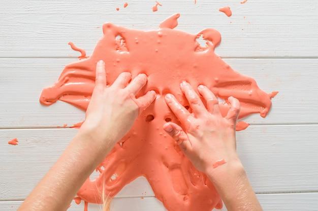 Девушка тасует своими руками оранжевую слизь на белом столе.