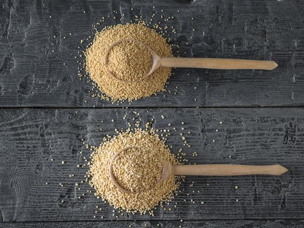 キノアの種子と木のスプーンとアマランスの種子と木のスプーン。グルテンフリー食品。
