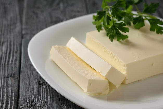 木製のテーブルの上にボウルにパセリの葉とセルビアのチーズをカットします。