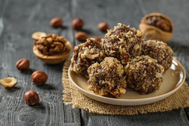 ドライフルーツ、ナッツ、木製のテーブルの上のチョコレートの手作りボール。