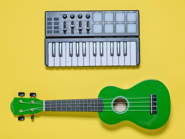 黄色の背景に緑のウクレレと音楽ミキサー。上からの眺め。