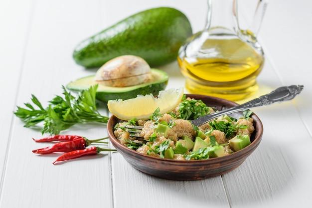 テーブルの上のオリーブオイルとアマランスの種子、アボカド、パセリのサラダ。