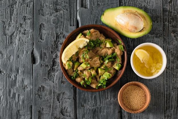 アマランスの種サラダ、アボカド、レモン、トマト、黒いテーブルにオリーブオイルのボウル。上からの眺め。