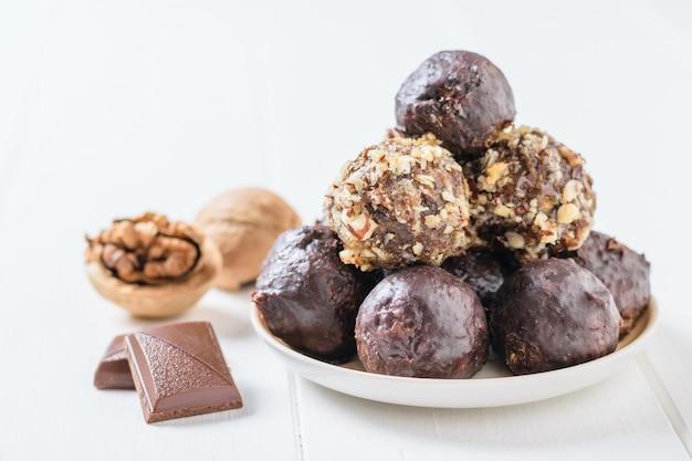 クルミ、チョコレートのかけら、ナッツのボール、ドライフルーツ、黒いテーブルの上のチョコレート。美味しくて自家製のキャンディー。