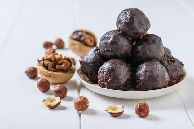 すりおろしたナッツとドライ木製のボウルに白い木製のテーブルの上にチョコレートが降り注ぐボール。美味しくて自家製のキャンディー。