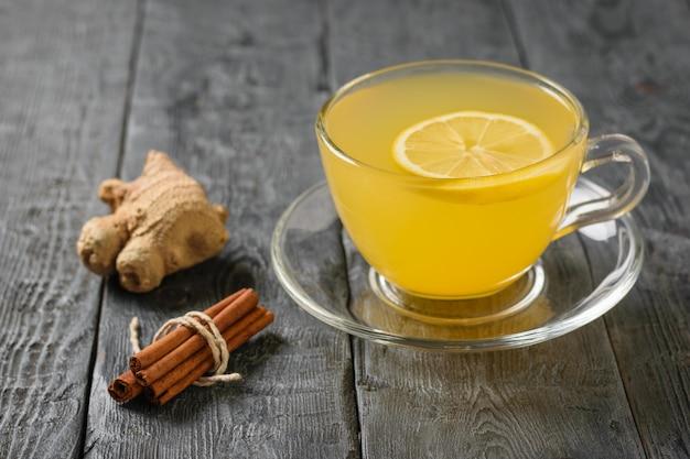 シナモンスティックの束、生姜の根、黒いテーブルの上に生姜と柑橘類の飲み物。