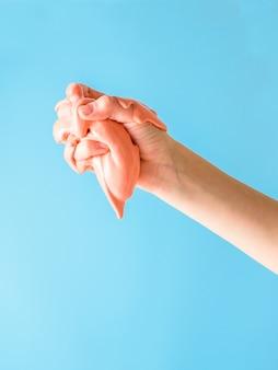 Правая рука ребенка разминает оранжевую слизь на синем.