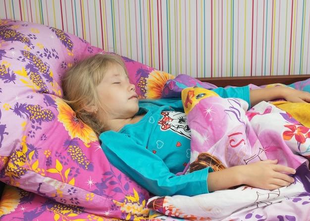 Маленькая красивая девушка в постели.