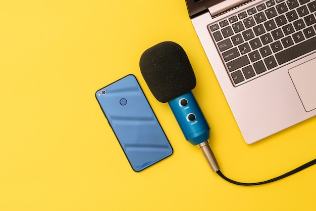 黄色のノートパソコンの近くの青と青のスマートフォンマイク