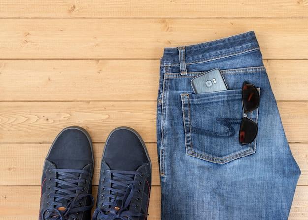 木製の床にメンズジーンズとアクセサリー。