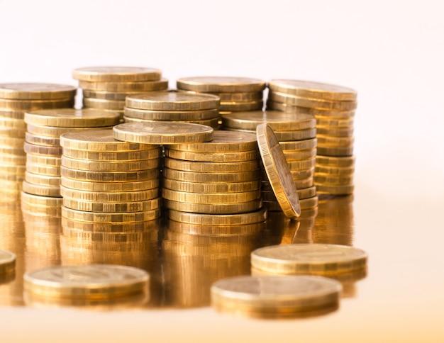 Металлические монеты сложены на золотом столе.