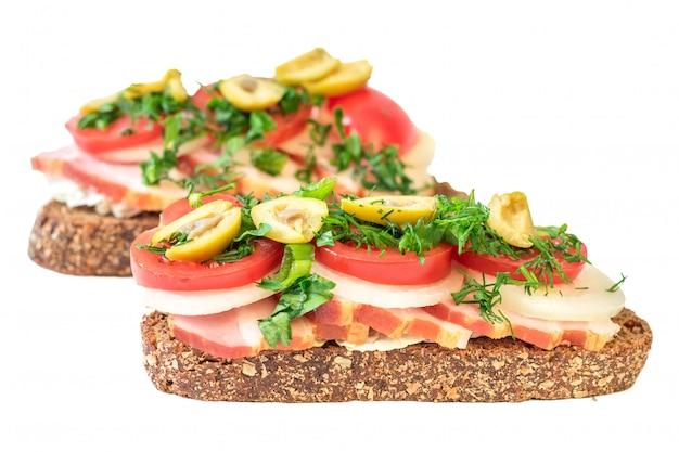 白で隔離されるハムと作りたてのサンドイッチ。