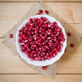 木製のテーブルの上にボウルにザクロの種子。