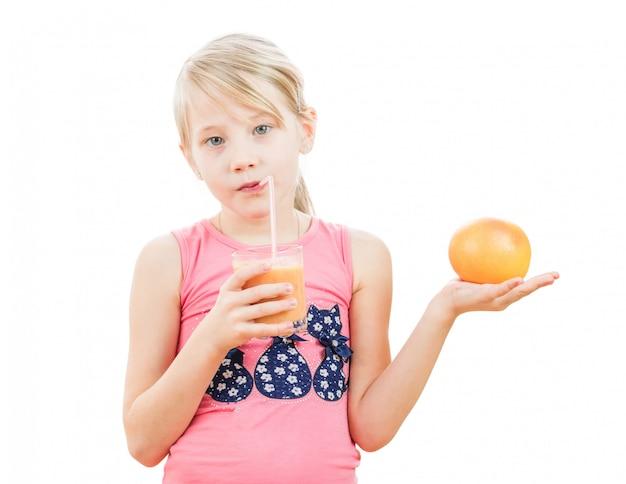 スムージードリンクの手でグレープフルーツを持つスポーツ少女。
