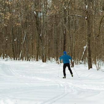 美しい冬の森と青いスーツのスキーヤー。