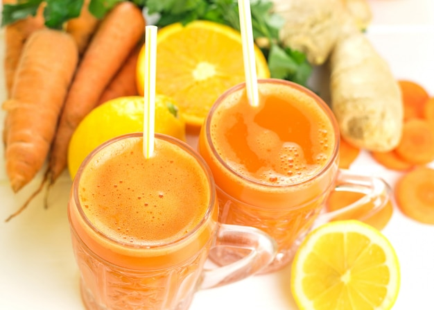 Две стеклянные кружки с морковным смузи и коктейльной соломкой.