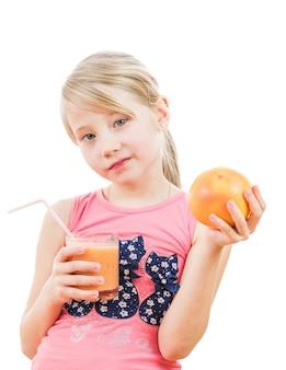 ピンクの女の子はグレープフルーツのスムージーを保持しています。