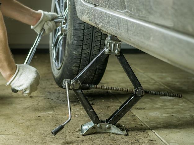 男性の手がガレージで車のホイールを回転させました。