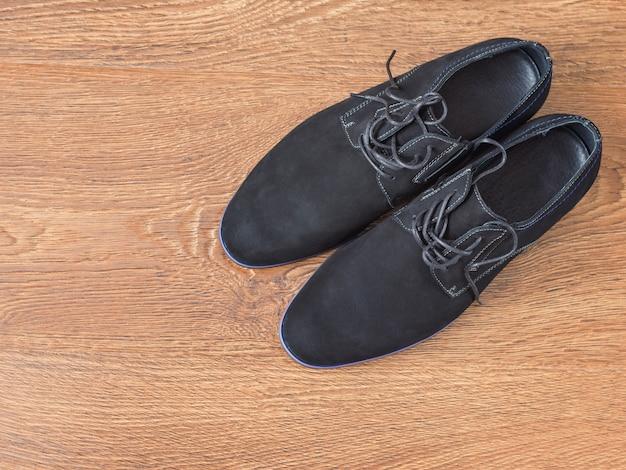 木製の床に黒のメンズシューズ。