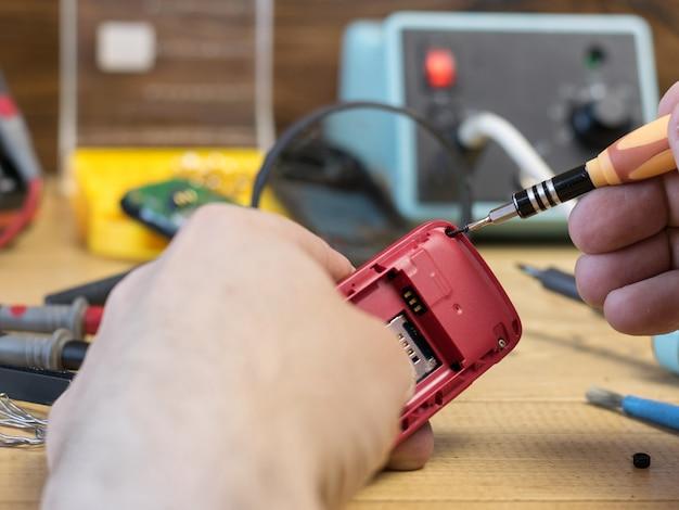 男が修理のために携帯電話を調べます。