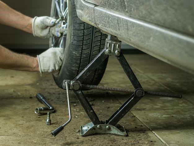 男はガレージで茶色の車の車輪を取ります。