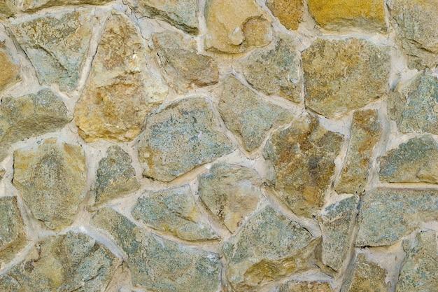 Фрагмент искусственно сделанной стены из камня и связующего раствора.