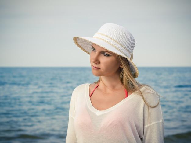 Красивая женщина в белой шляпе с распущенными волосами