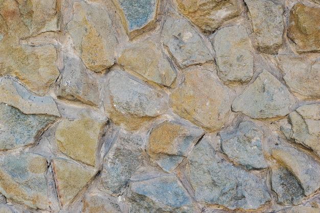 モルタルに置かれた大きな美しい石の背景の壁。