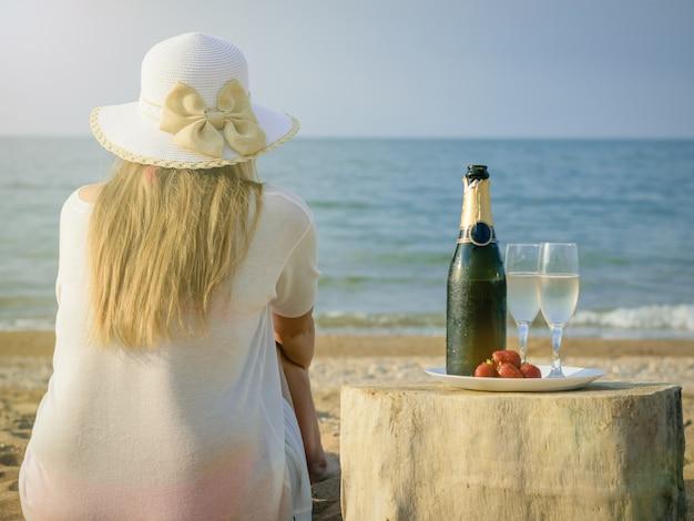 Женщина в шляпе на море с открытой бутылкой шампанского и двумя бокалами.