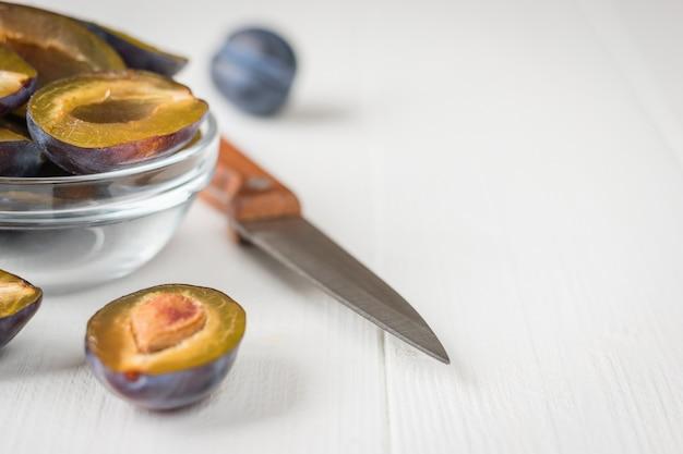 Ягоды сливы в стакане часто с ножом на белом деревянном столе.