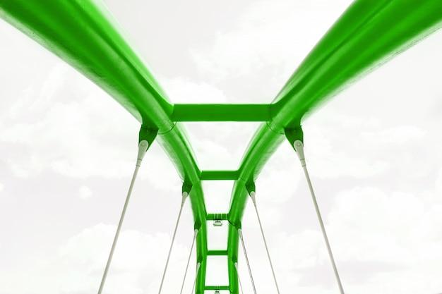 Взгляд верхней структуры зеленого моста против голубого неба.