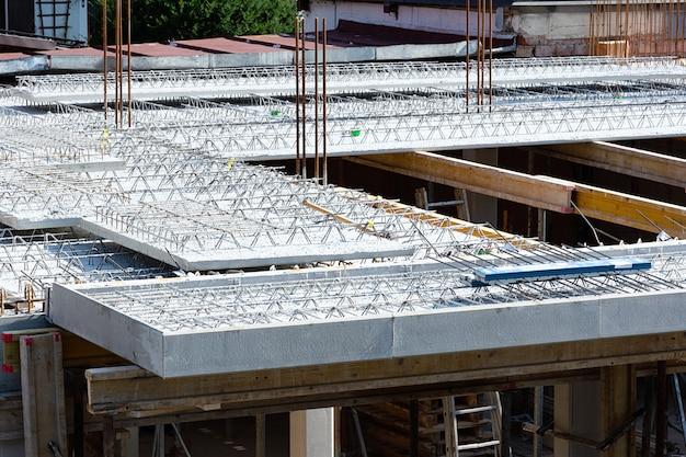 Вид на бетонные плиты и арматуру на строительной площадке жилого дома.