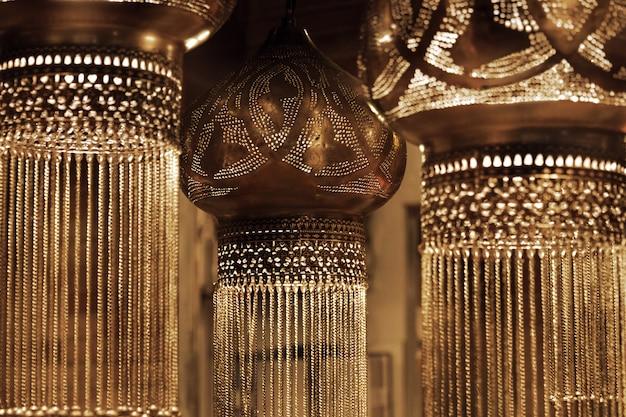 金色の輝きで暗いヴィンテージ東洋吊りランプ。