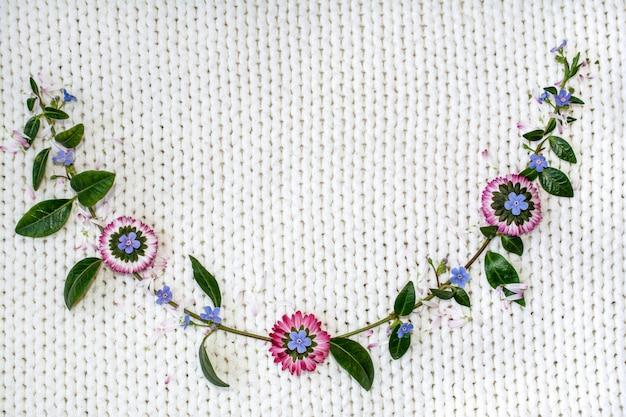 ニット生地の白い背景の上の花。