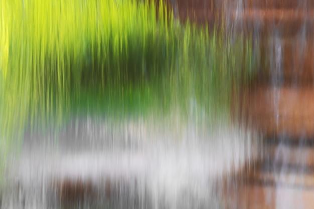 森の背景の噴水から流れる水。
