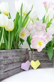 Букет из розовых и белых тюльпанов в деревянной коробке и бумажные сердечки желтого и сиреневого цвета на белом фоне.