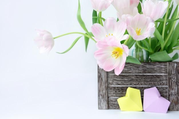 Букет из розовых тюльпанов в деревянной коробке и двух бумажных сердец желтого и сиреневого цвета на белом фоне.