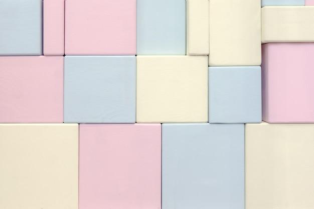 Стенка из дерева прямоугольной формы разного размера сине-желтого и розового цвета.