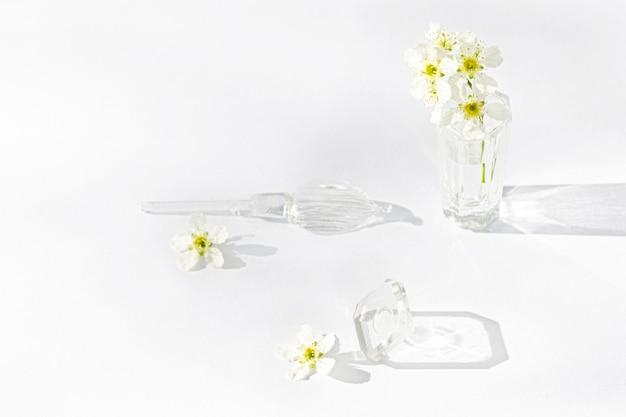 透明な香水のボトルと白い花の小枝、その隣にはガラス棒とキャップがあります。