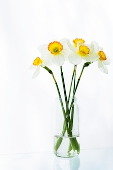 白い水仙の花の花束はテーブルの上の水の瓶に立っています