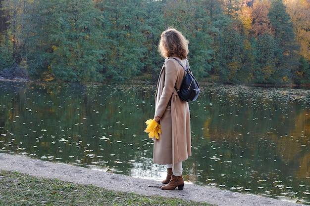 Осень. молодая женщина стоит на берегу озера и смотрит вдаль. она одета в модную деловую одежду бежевого цвета. в ее руках у нее букет кленовых листьев.